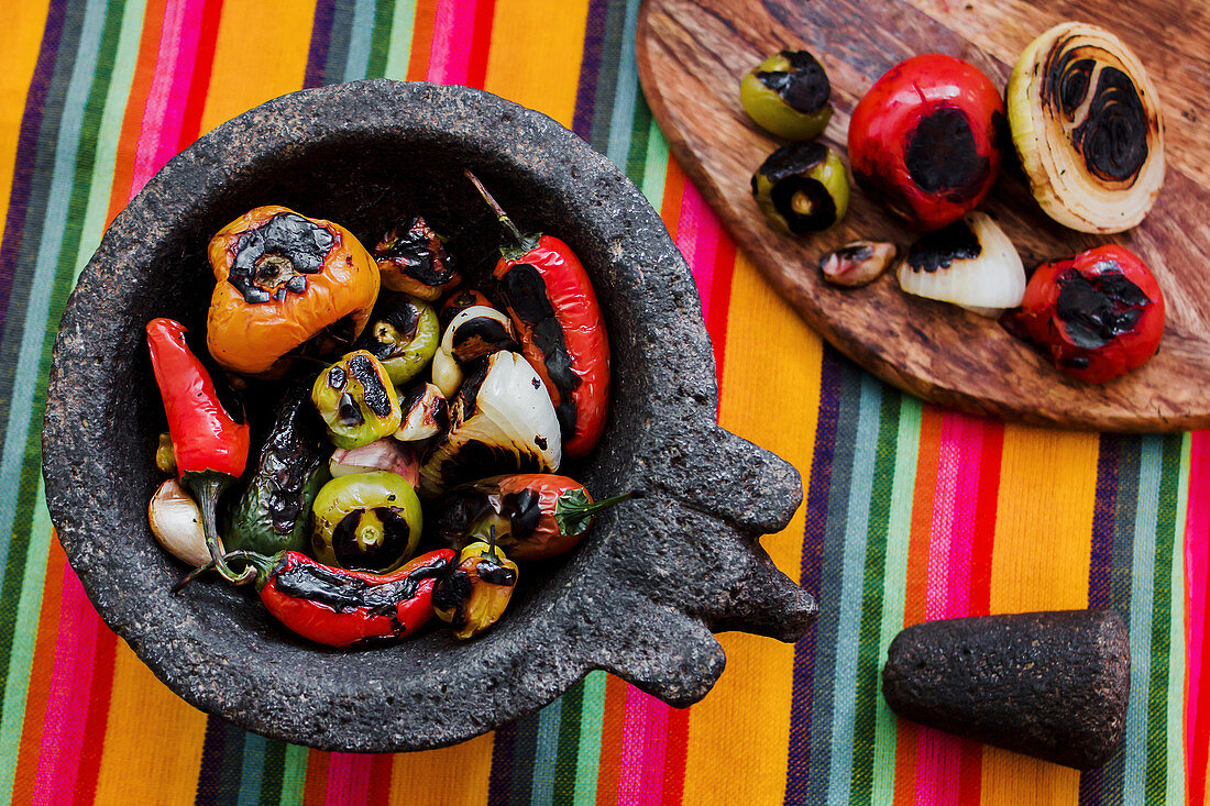 Roasted vegetables placed on black tray in colorful kitchen towel