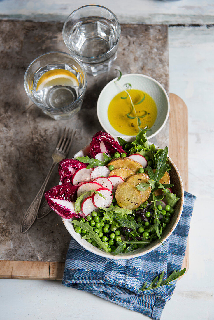 Veggie bowl with radishes, baked potatoes, peas, arugula, lettuce, radicchio and olive oil