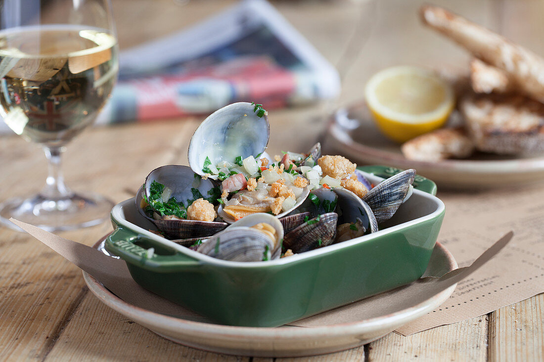Clams with bacon and white wine sauce served with sourdough bread and white wine