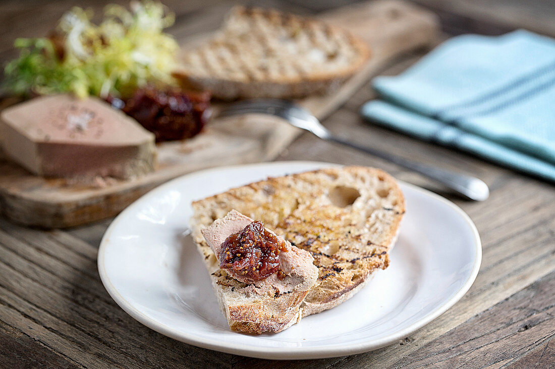 White plate with pate on toast, wooden board in background