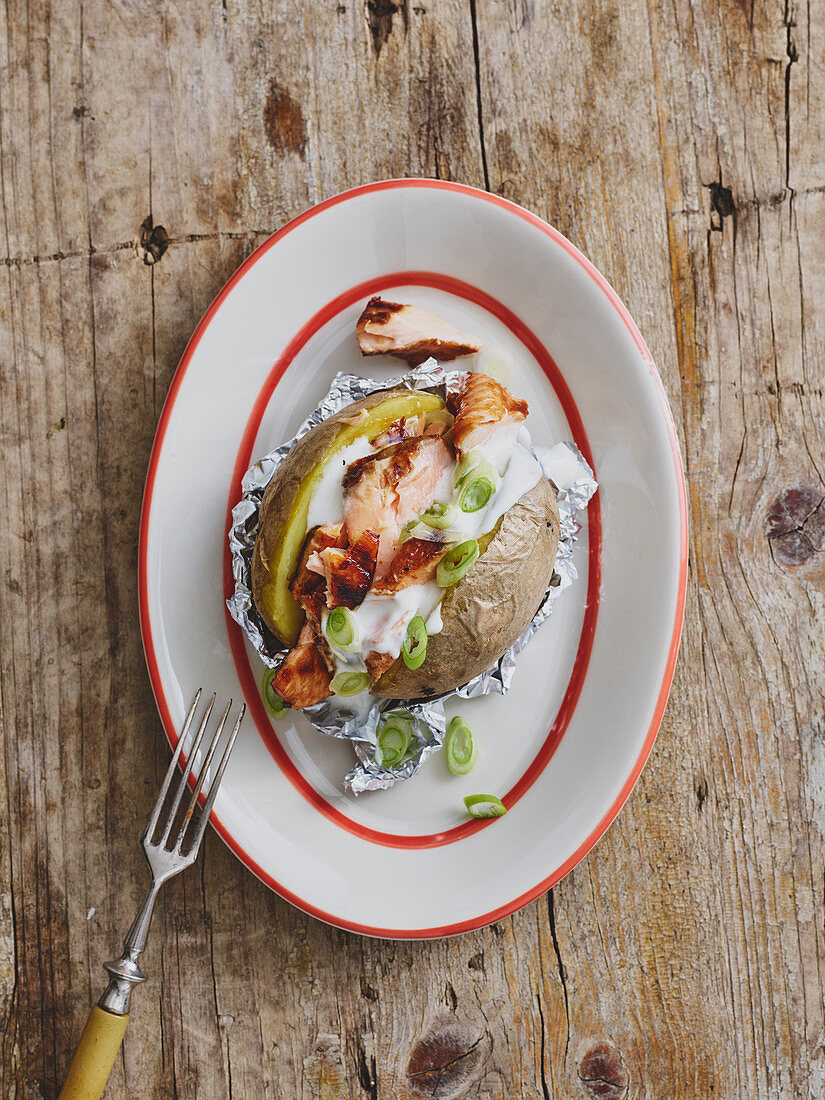A jacket potato with grilled salmon and sour cream