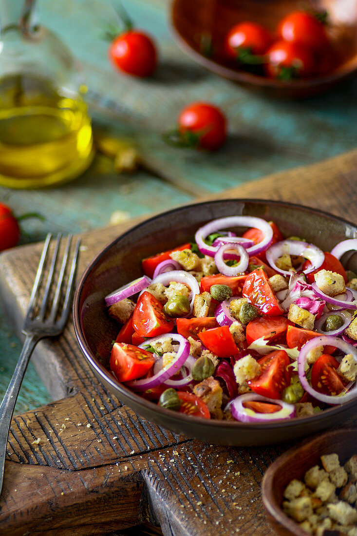 Cherry tomatoes salad with red onion, croutons, capers, and mix of salads