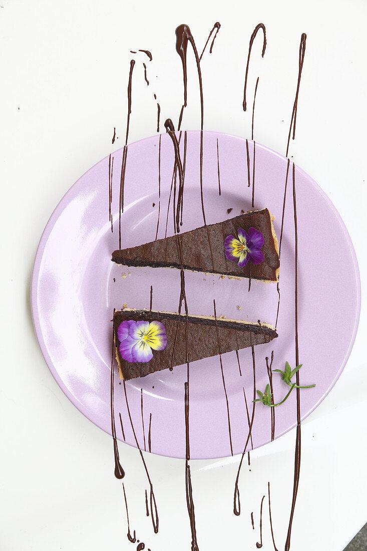 Zwei Stücke Schokoladentarte mit Hornveilchen