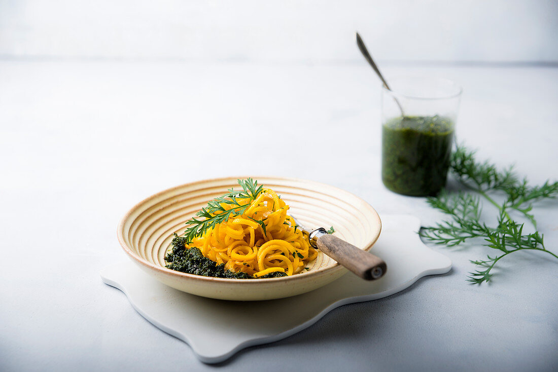 Yellow carrot spirals with vegan pesto made form carrot leaves