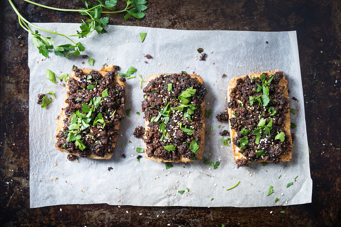Tofu topped with black breadcrumbs, garnished with parsley and sesame seeds (vegan)