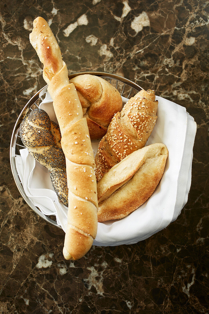 A basket of bread on a marble table