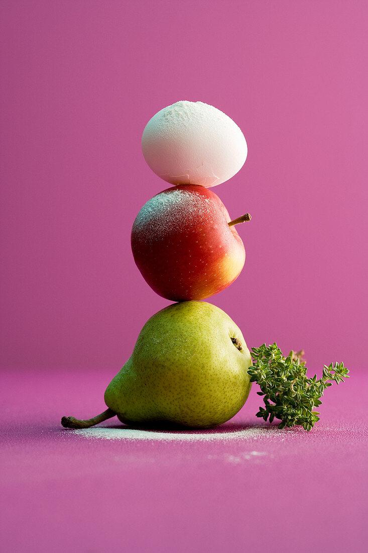 Stapel aus Birne, Apfel und Ei mit Thymian
