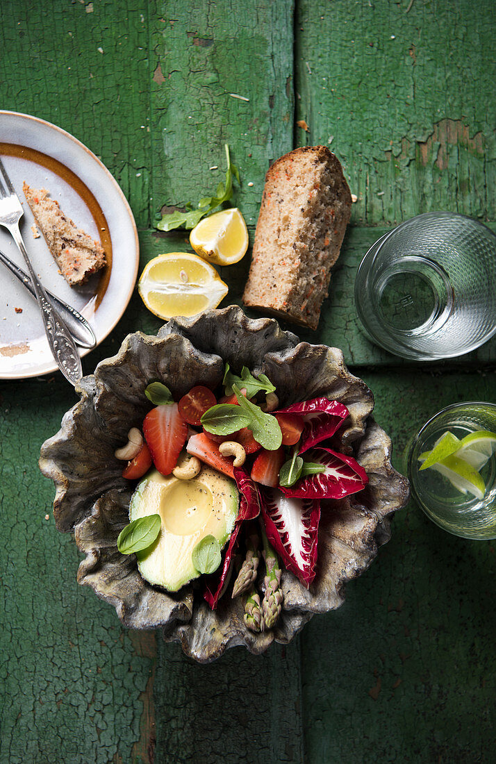 Radicchio with avocado, cashew nuts, strawberries, tomatoes and rocket served with carrot bread