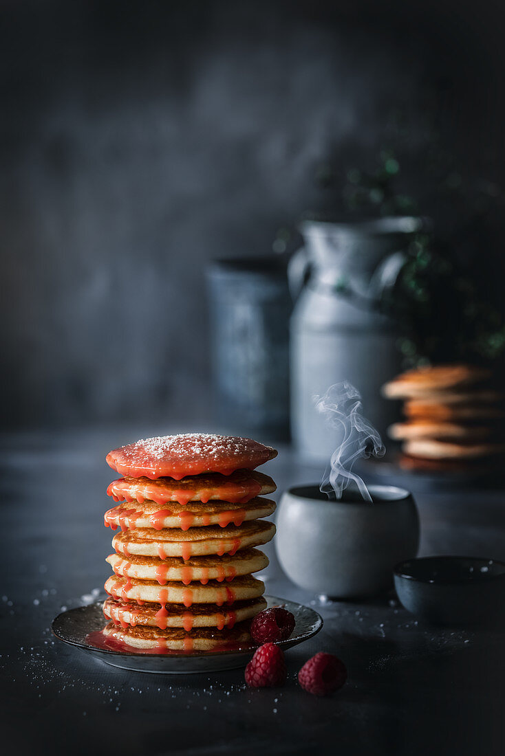 A stack of pancakes with raspberry sauce