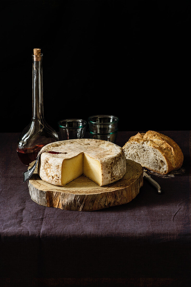 A wheel of unpasteurized Spanish cheese with a slice cut out