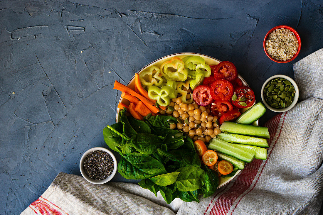 Buddha bowl with chickpea, baby spinach and other organic vegetables on concrete background