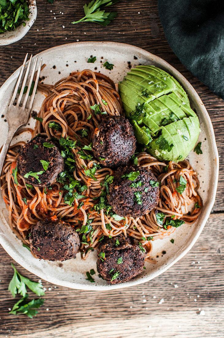 Vegan black bean balls with soba noodles, ajvar and parsley