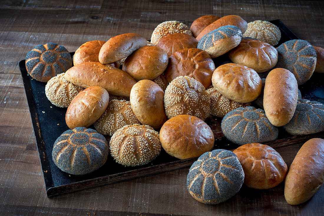 Various buns, sesame seeds and poppyseeds, on a baking tray