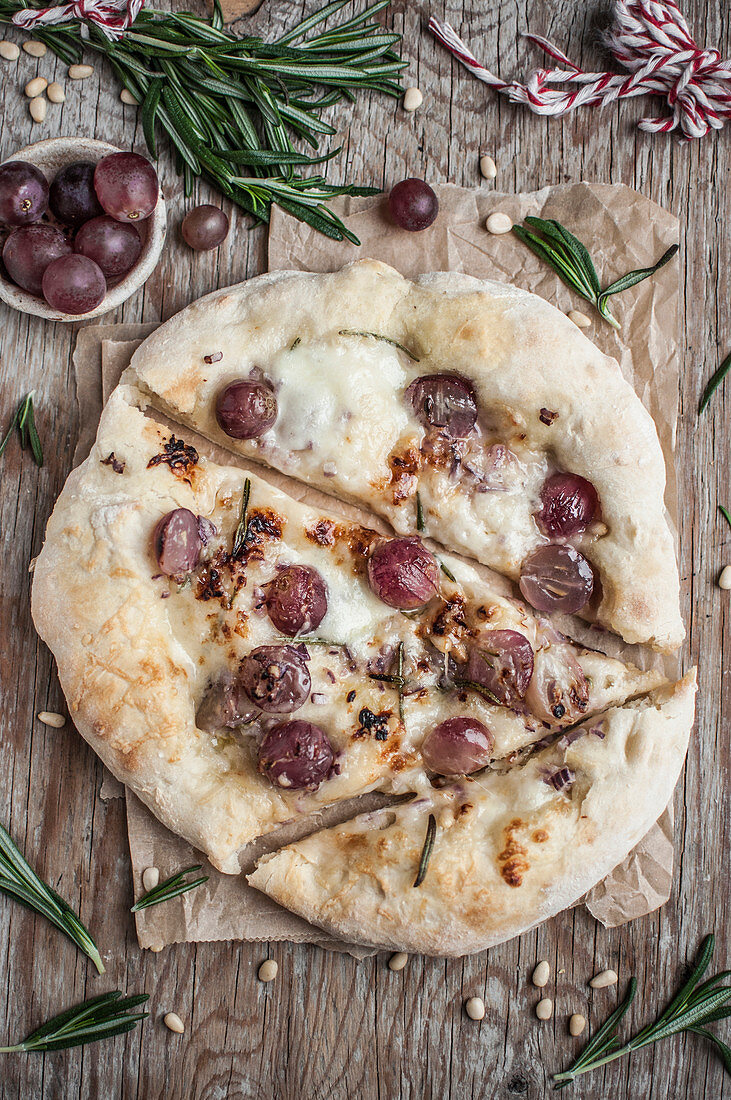 Homemade pizza with grapes and rosemary