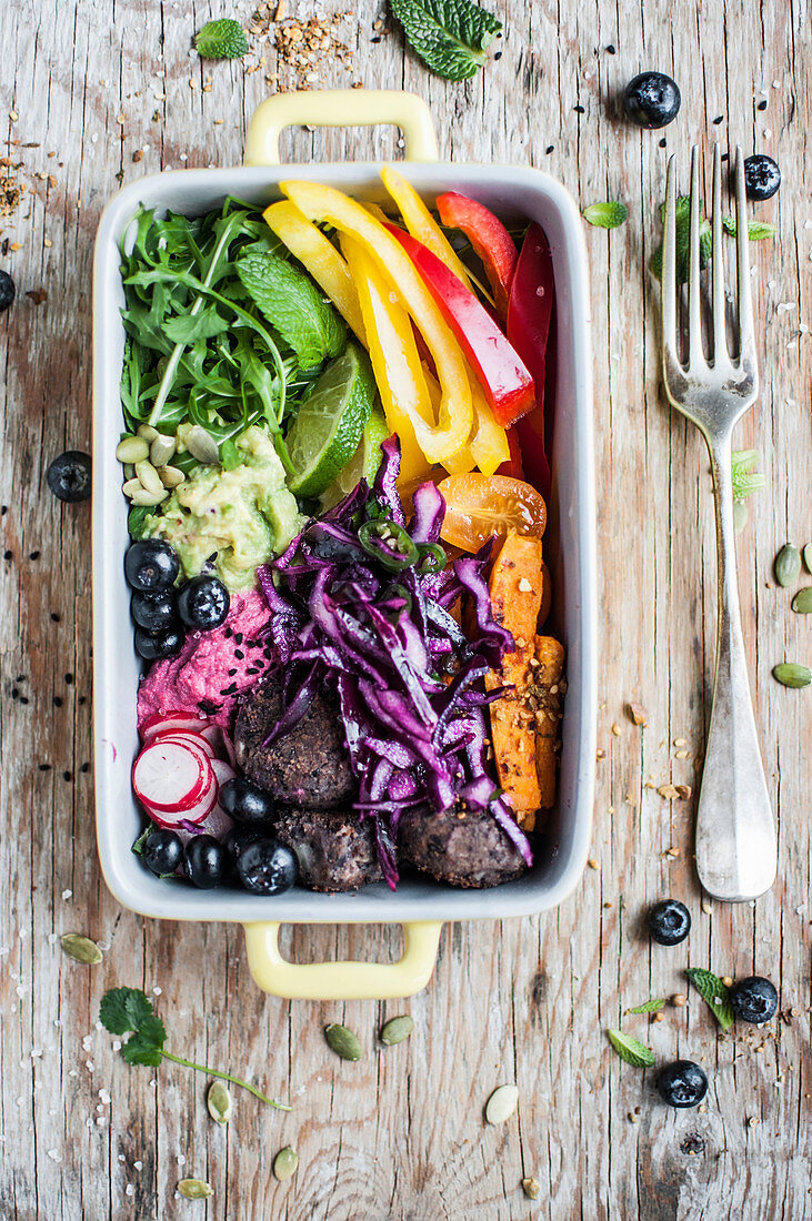 Rainbow vegan buddha bowl with black bean balls