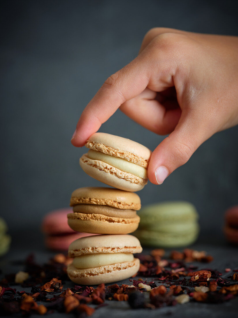 Hand taking a macaron from a pile
