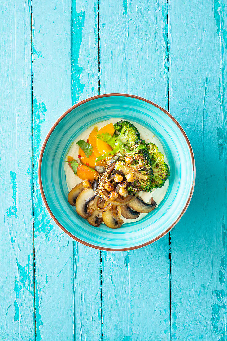 A vegan hummus-cashew bowl with fried broccoli, mushrooms and chilli apricots