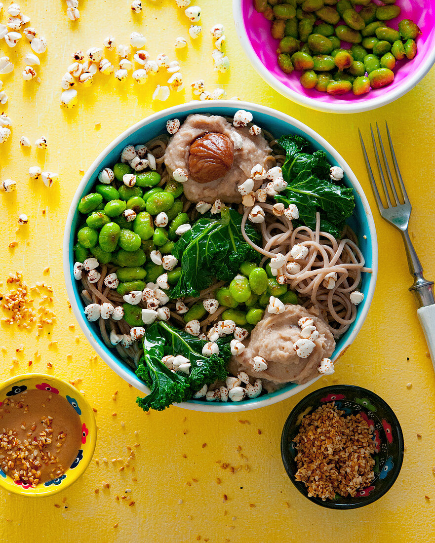 A bowl of edamame, soba noodle, chestnut purée, kale, sesame seeds and buckwheat pops