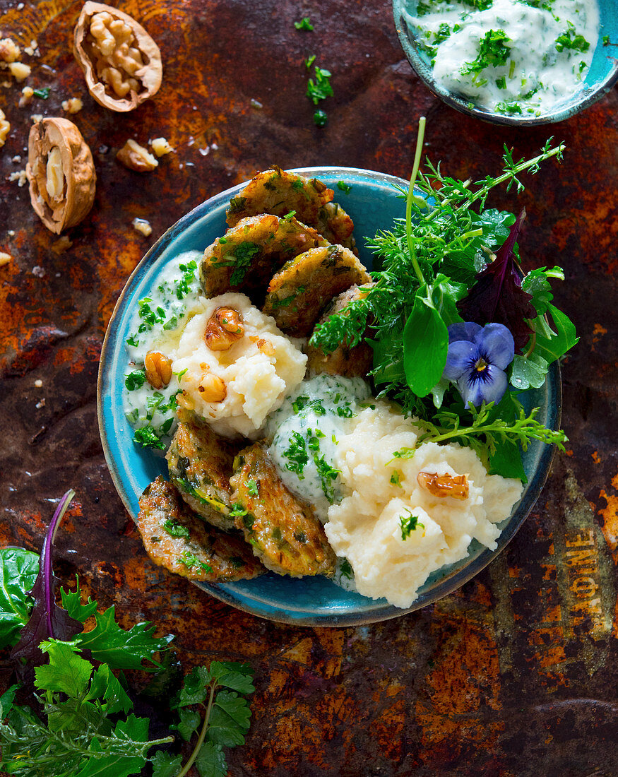 A bowl with potato fritters, parsnip purée, parsley yoghurt, garden salad and walnuts