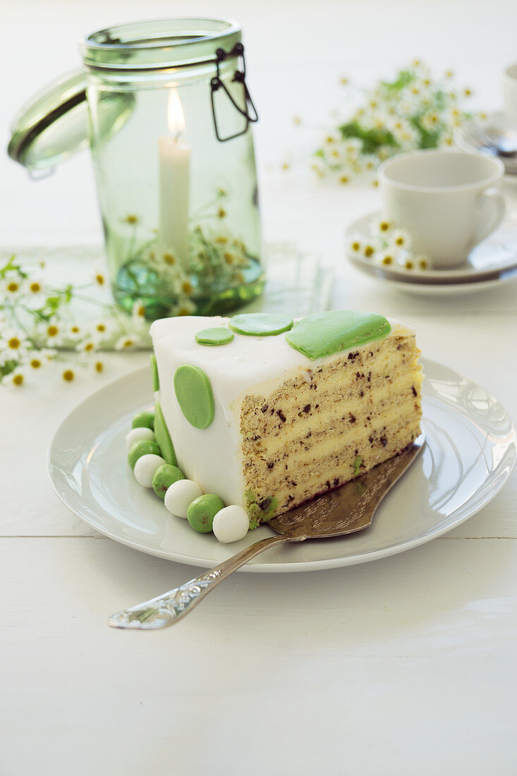 Piece of butter cream cake with fondant, camomile blossoms and a candle