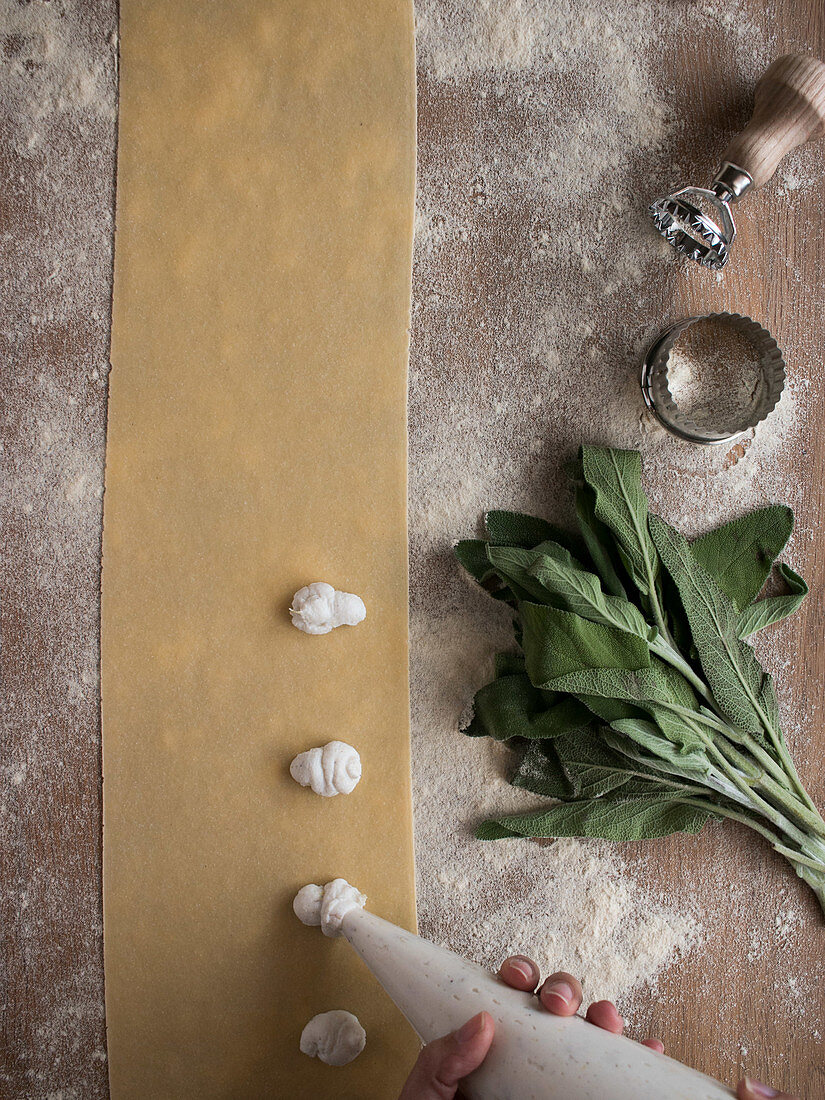 Hands of anonymous cook squeezing creamy filling on thin ravioli dough near bunch of fresh sorrel