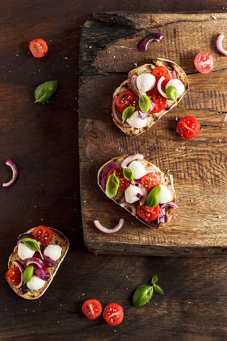Bruschetta with mozzarella, red onion, strawberry tomatoes nad fresh basil