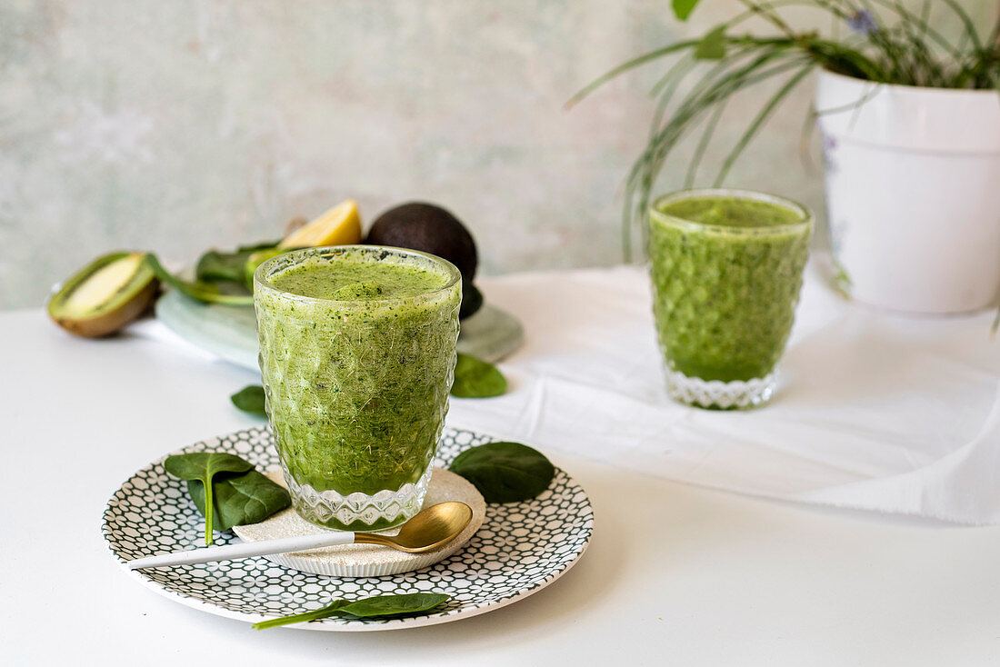 Healthy green smoothie - spinach, avocado and kiwi apple with lemon juice