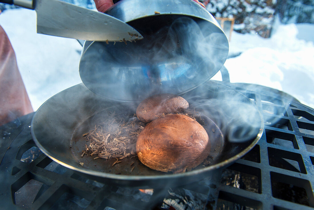 A winter barbecue: portobello mushrooms being smoked on a barbecue (Norway)