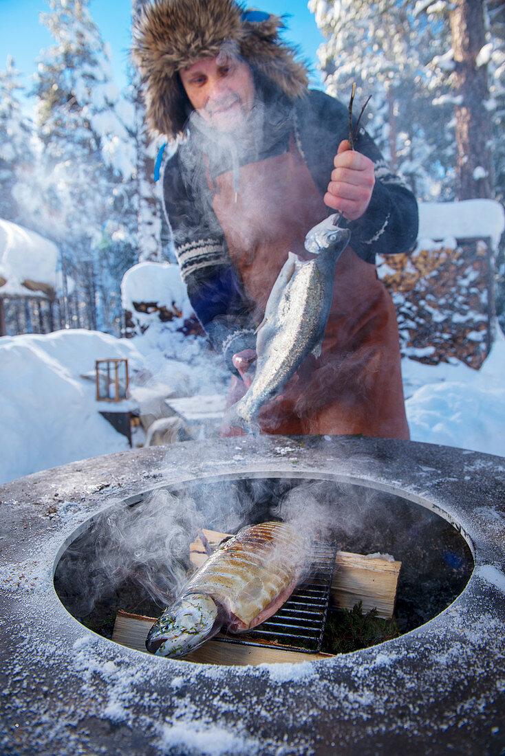 Winter barbecue: a man smoking salmon (Norway)