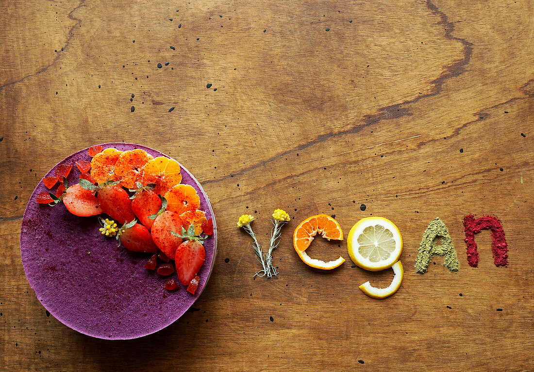 Word 'vegan' laid out of fruits and berries, green tea matcha powder, red lyophilised berries