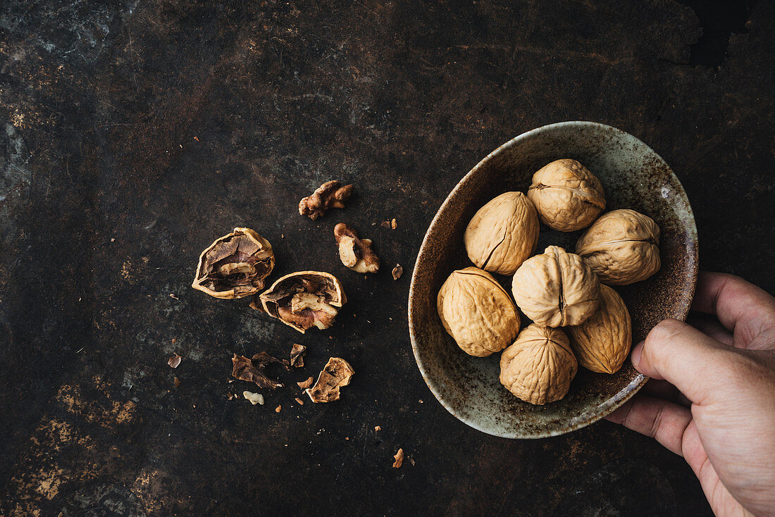 A hand holding a bowl of walnuts