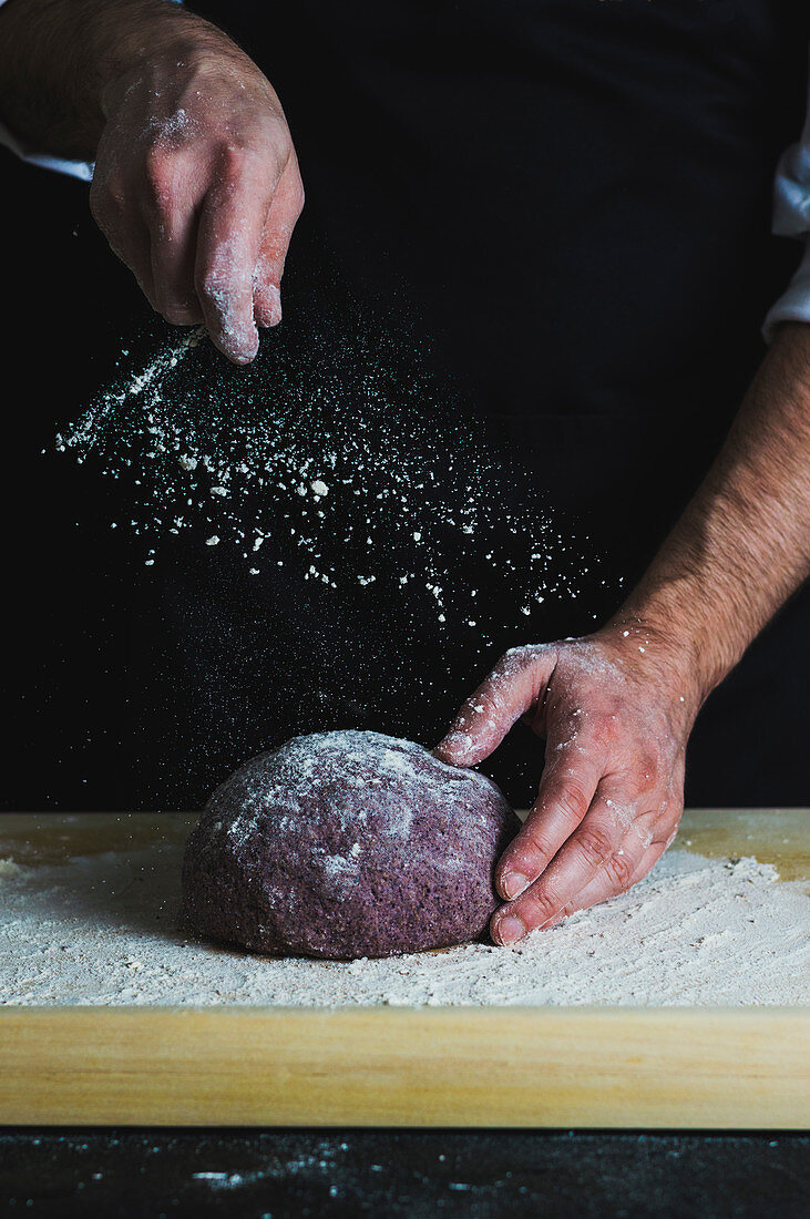 Purple loaf of spelt aronia berry powder bread being dusted with flour