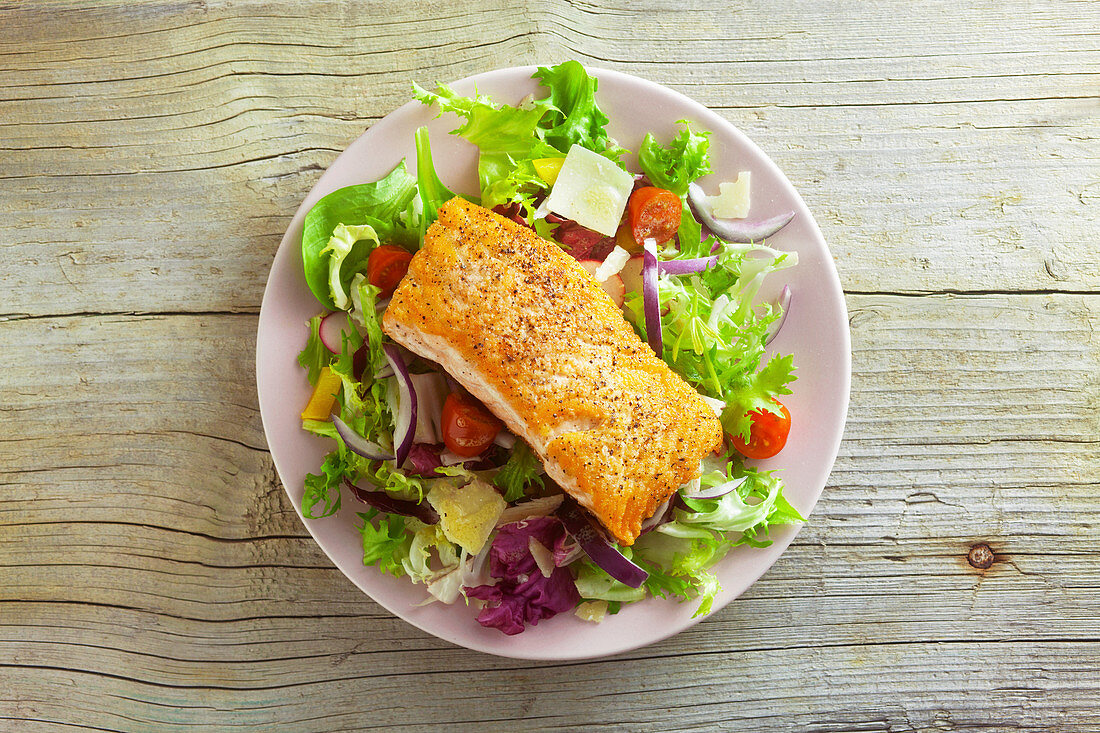 Mixed leaf salad with fried salmon fillet (seen from above)