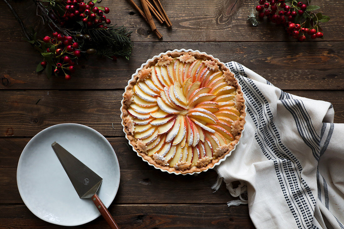 Tasty apple pie on a wooden table ready to eat near empty plate