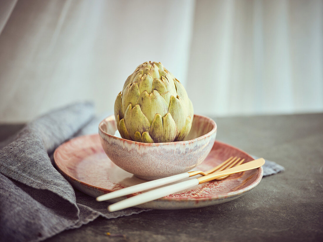 Small knife and fork and whole fresh artichoke placed on pink ceramic plate on table