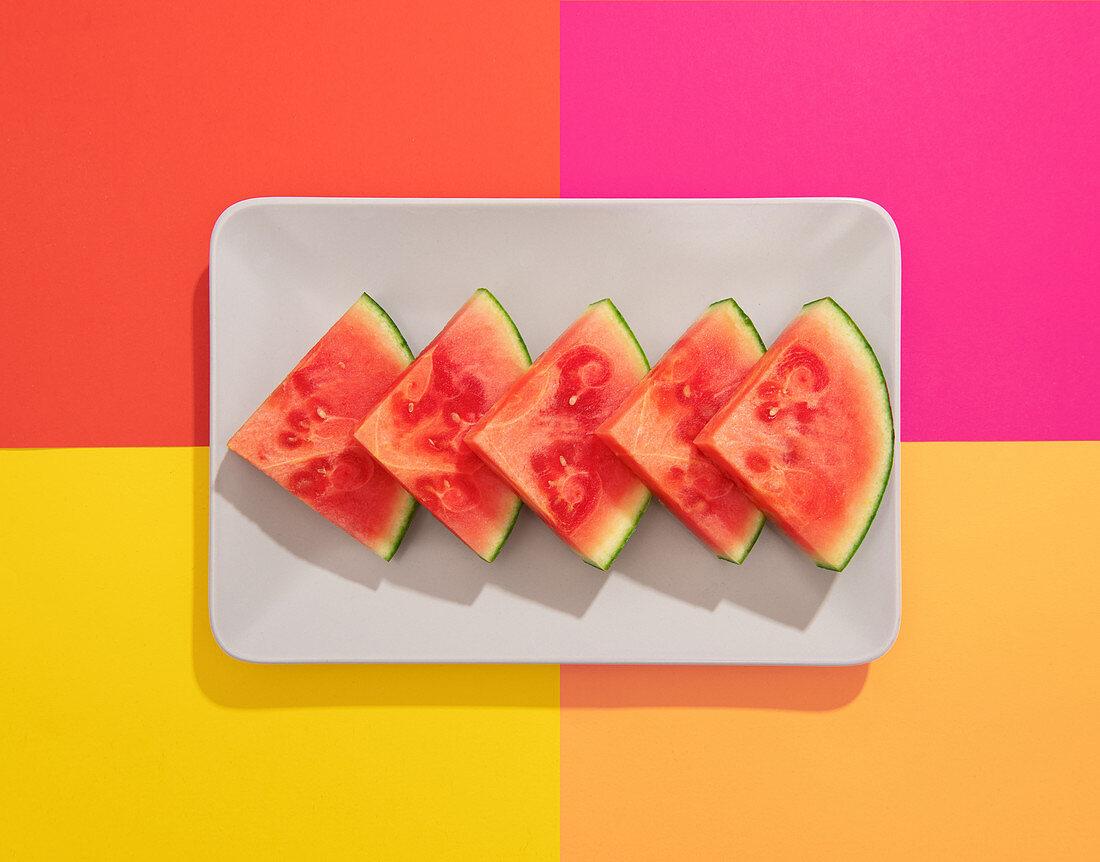 Weißer Teller mit Wassermelonenschnitzen auf buntem Untergrund