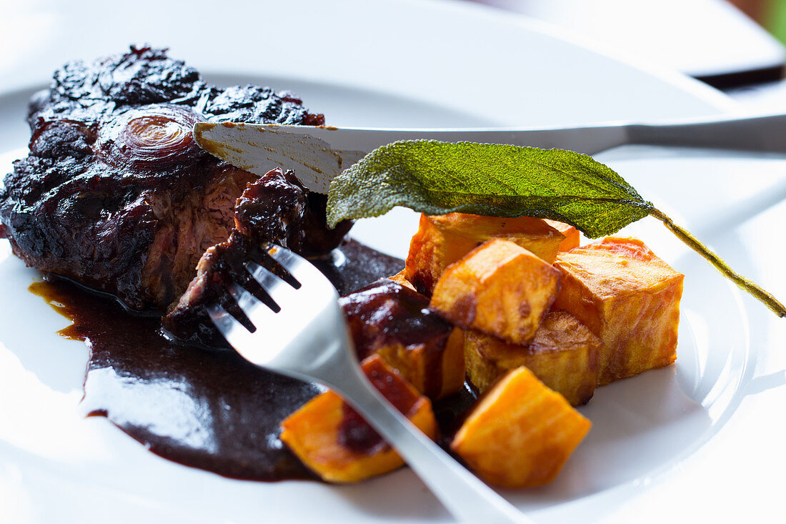 Oxtails in red wine gravy with fried sweet potatoes and a sage leaf