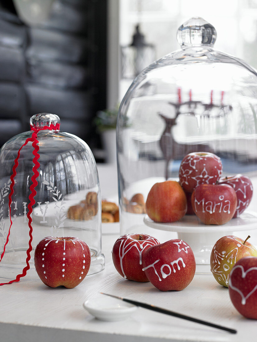 Apples decorated with icing patterns and letters under glass cover