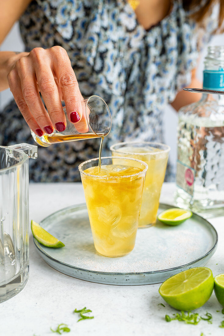 Pouring Grand Marnier into a Cadillac Margarita on the rocks in a glass