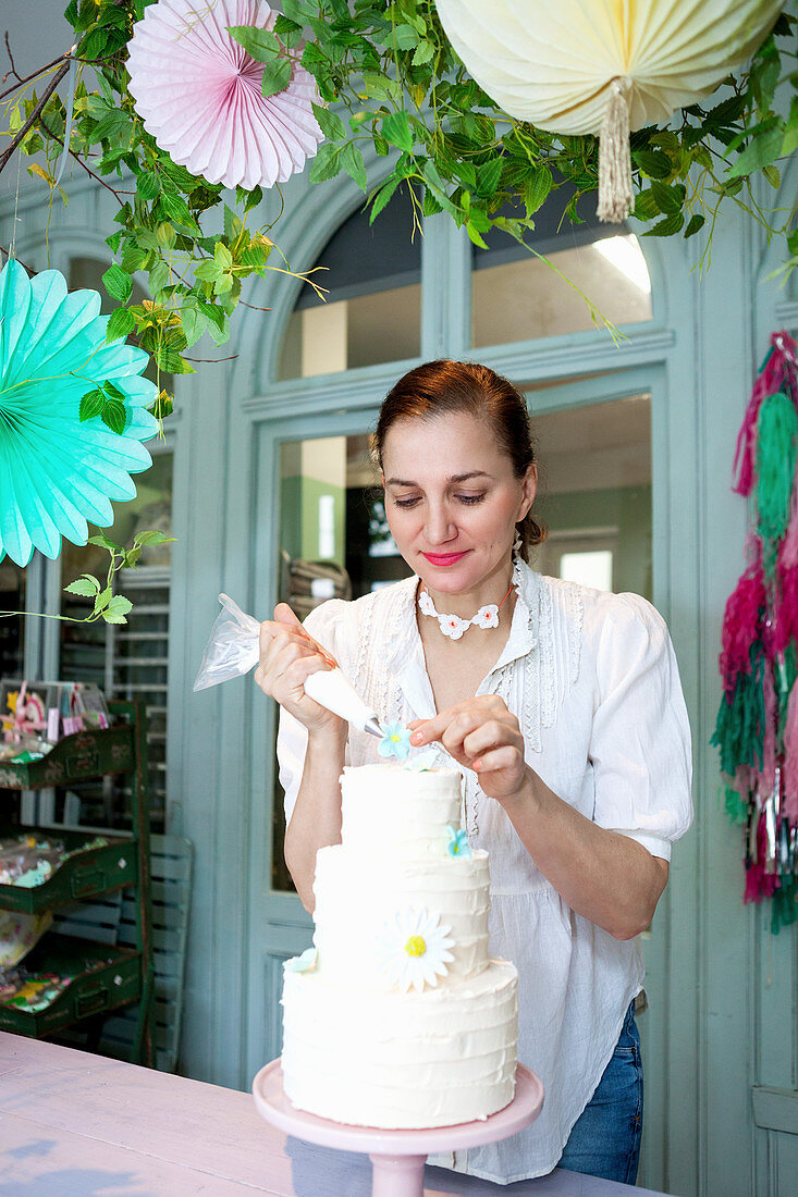 Nadja Bruhn decorating three-tiered cake in biscuit workshop