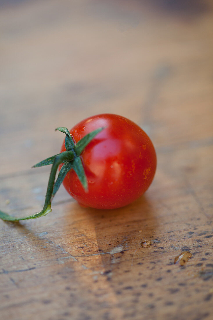 A tomato on a wooden surface