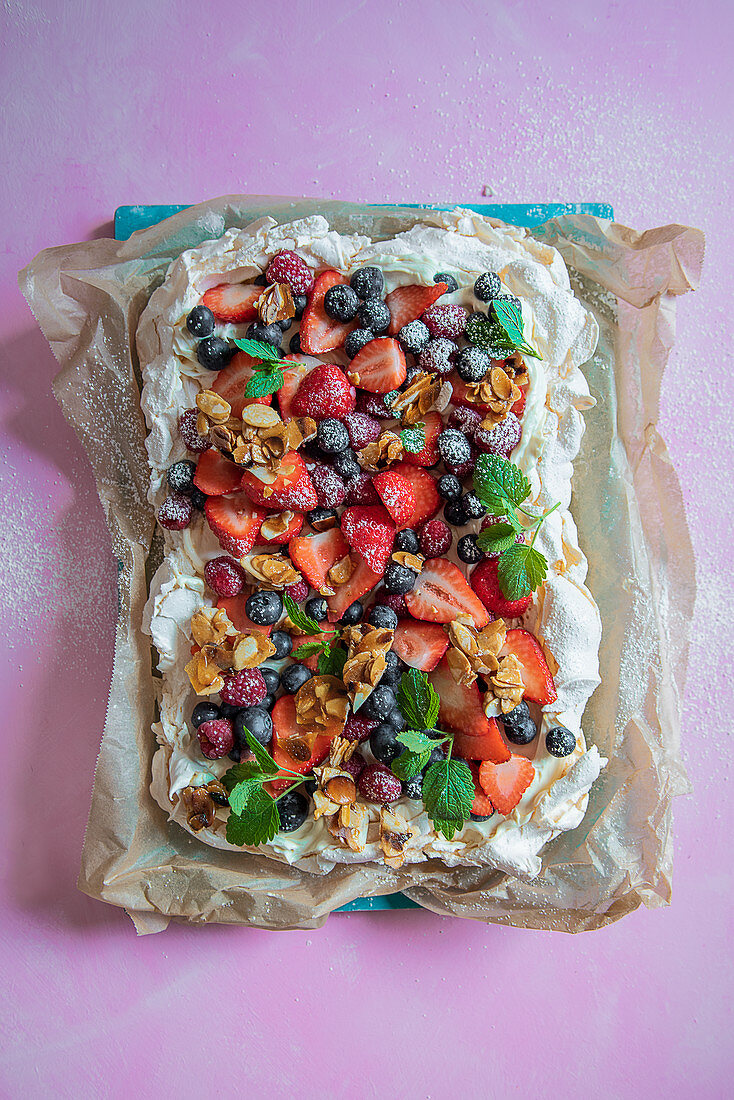 Pavlova with cream, fresh berries and almond brittle
