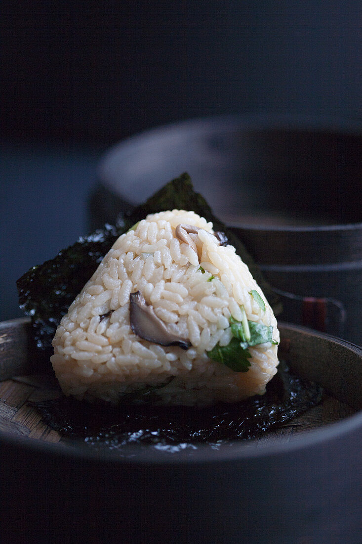 Onigiri with mushrooms and green shiso on a salty nori leaf (Japan)