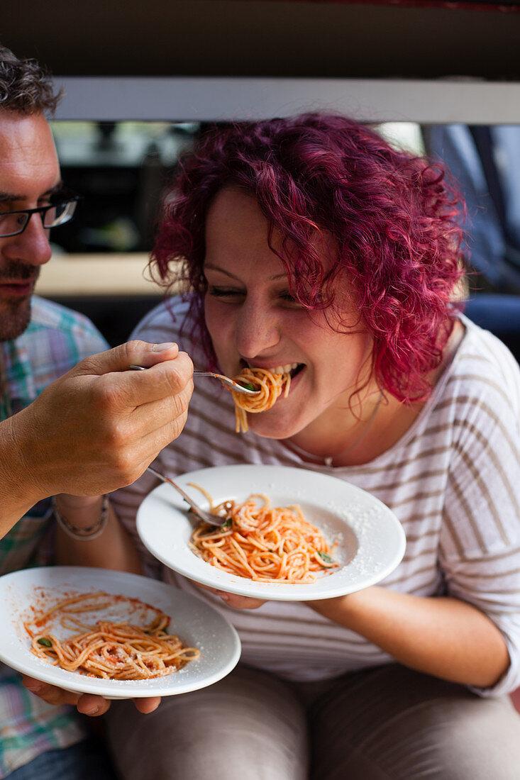 Paar isst Spaghetti vor dem Campingwagen