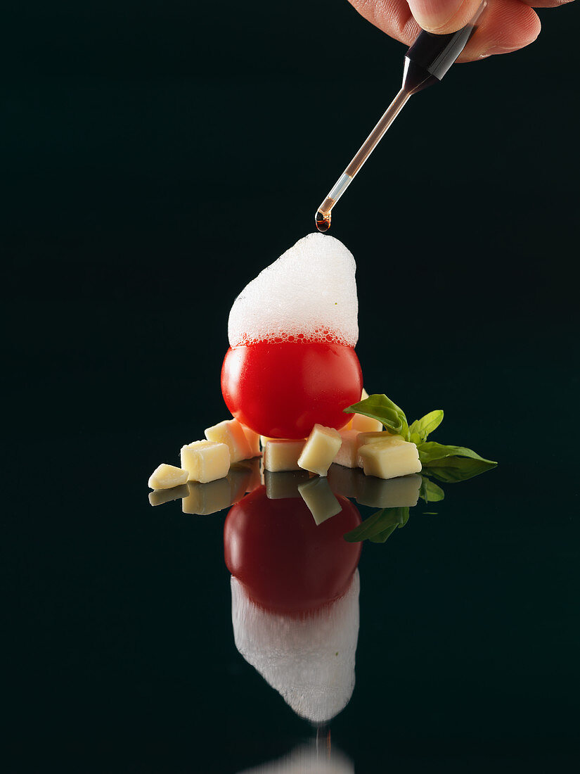 Basi aiir on a cherry tomato with chocolate (molecular gastronomy)