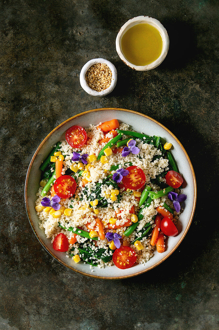 Couscous with parboiled vegetables baby carrots, green beans, sweet corn, spinach served in ceramic plate with tomatoes, sesame and edible flowers