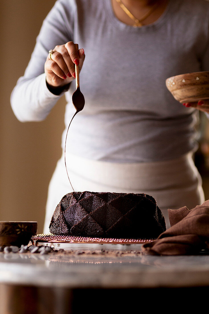 A woman decorating a Gluten-free Chocolate Budnt cake with chocolate drizzle