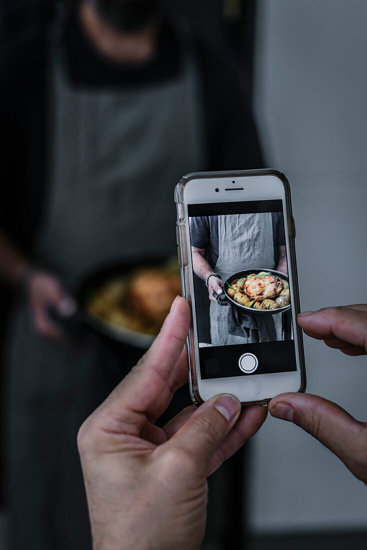 Crop person hand taking pictures on mobile phone tasty dish in hands of faceless man