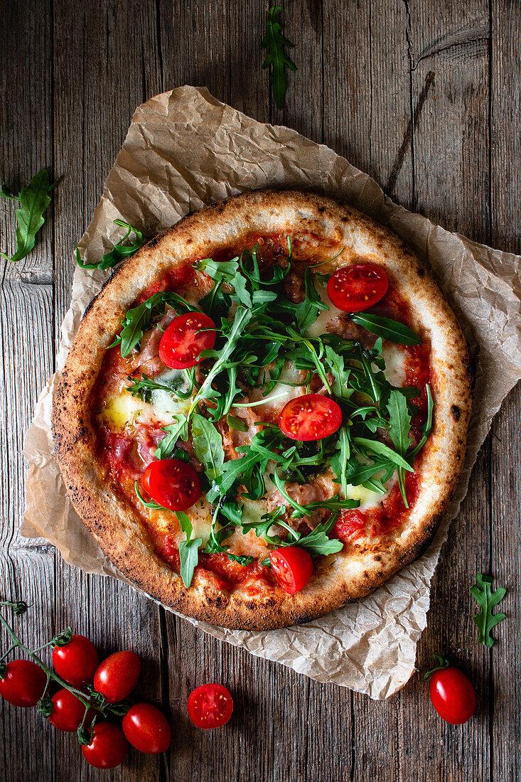 Ganze Schinken-Käse Pizza mit frischen Tomaten und Rucola