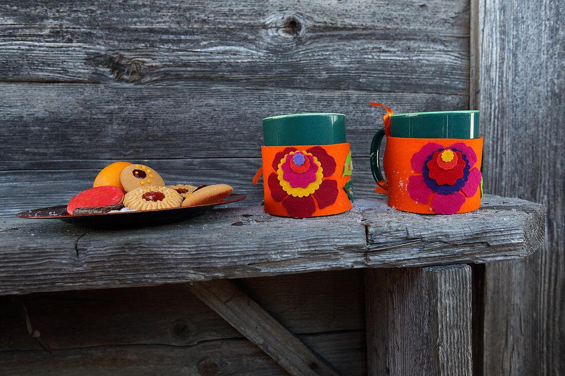 Handmade felt mug cosies with colourful floral mtifs